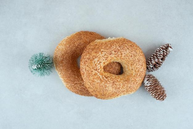 Zwei leckere bagels mit kleinem weihnachtsbaum und tannenzapfen.