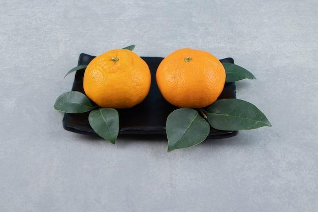Zwei leckere clementinenfrüchte auf schwarzem teller