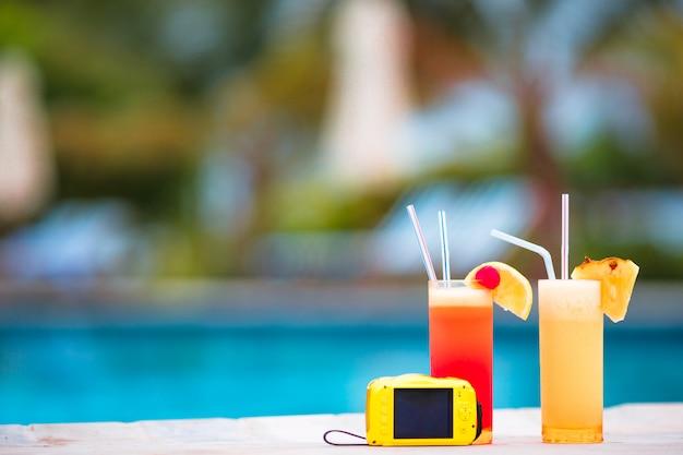Zwei leckere cocktails mit kamera am tropischen weißen strand