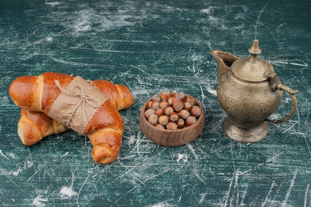 Zwei leckere croissants mit nüssen und altem wasserkocher.