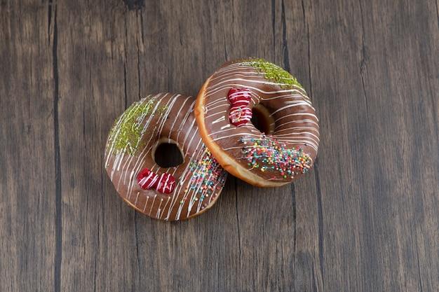 Zwei leckere donuts mit schokoladenglasur auf holztisch.