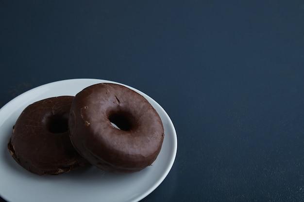 Zwei leckere frisch gebackene donuts, glasiert mit schokolade auf weißem keramikkleinteller lokalisiert in der ecke des rustikalen alten blauen holztisches