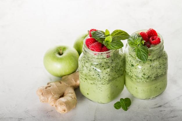 Zwei leckere grüne smoothies mit erdbeeren