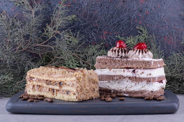 Zwei leckere kuchen auf dunklem teller mit kaffeebohnen. foto in hoher qualität
