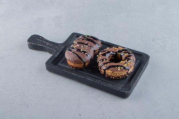 Zwei leckere mini-schokoladenkuchen und donut auf schwarzem schneidebrett