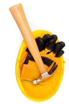 Zwei lederhandschuhe und ein hammer, der in einem sturzhelm liegt