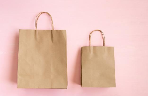 Zwei leere braune papiertüten mit griffen für den einkauf auf einem rosa hintergrund. kopieren sie platz. flach liegen.