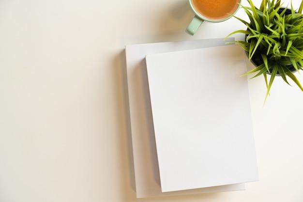 Zwei leere bucheinband für textanzeige mit kaffeetassenanlage und kopienraum auf weißem hintergrund
