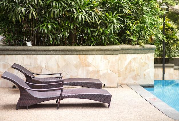 Zwei leere chaiselongues in der nähe von pool und tropischen palmen