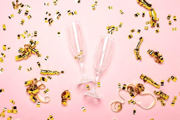 Zwei leere champagnergläser und goldene konfetti auf einem blassrosa