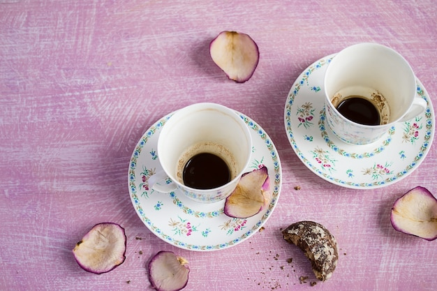 Zwei leere kaffeetassen und rosenblätter