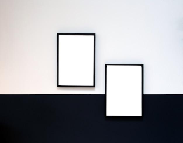 Zwei leere plakate, leinwand, rahmen hängen an schwarz-weiß-wand, innenarchitektur moderne modellrahmen kopieren raum,