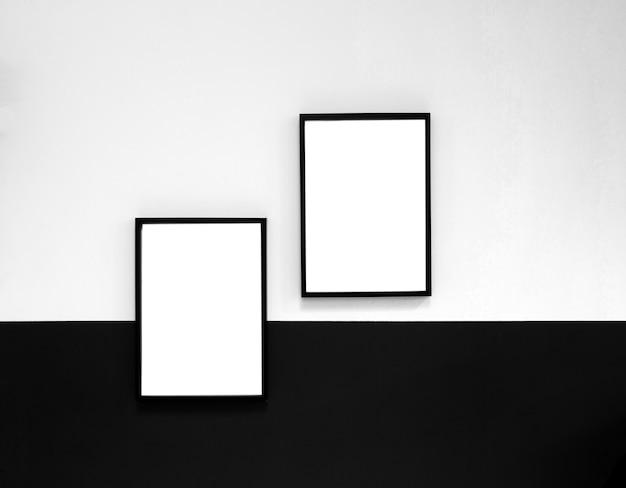 Zwei leere plakate, leinwand, rahmen hängen an schwarzweiss-wand, innenarchitektur moderne modellrahmen kopieren raum, raum für text