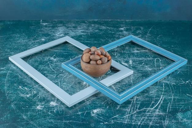 Zwei leere rahmen und eine schüssel mit verschiedenen nüssen auf blauem hintergrund. hochwertiges foto