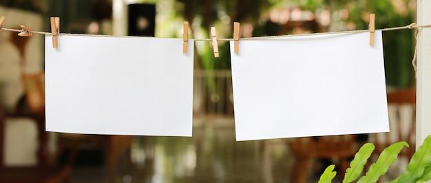 Zwei leere sofortige fotos, die an einer wäscheleine hängen.