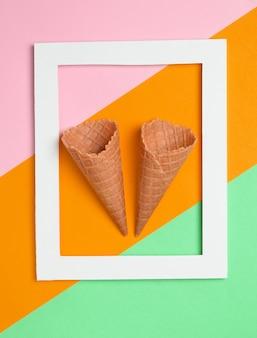 Zwei leere waffelhörner in einem weißen rechteckigen rahmen auf einem farbigen pastellhintergrund