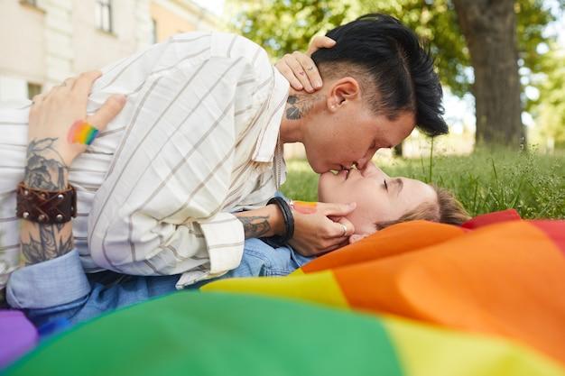 Zwei lesben, die auf grünem gras liegen und sich küssen, während sie zeit im park draußen verbringen