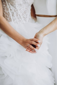 Zwei lesbische frauen, die sich an ihrem hochzeitstag an den händen halten