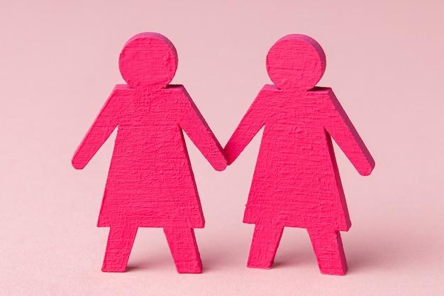 Zwei lesbische mädchen, die händchen halten. auf einem rosa hintergrund.