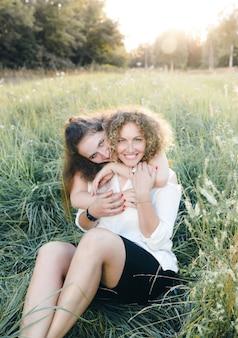 Zwei lesbische mädchen sitzen im gras im park und umarmen sich. gleichgeschlechtliche liebe. lgbt menschen