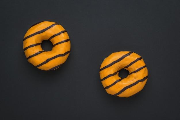 Zwei leuchtend orange donuts auf einem schwarzen hintergrund. leckeres beliebtes gebäck.