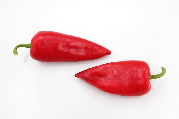 Zwei leuchtend rote paprika auf einem weißen