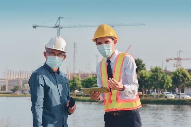Zwei leute, die am bau der baustelle arbeiten und dann über ein bauprojekt sprechen