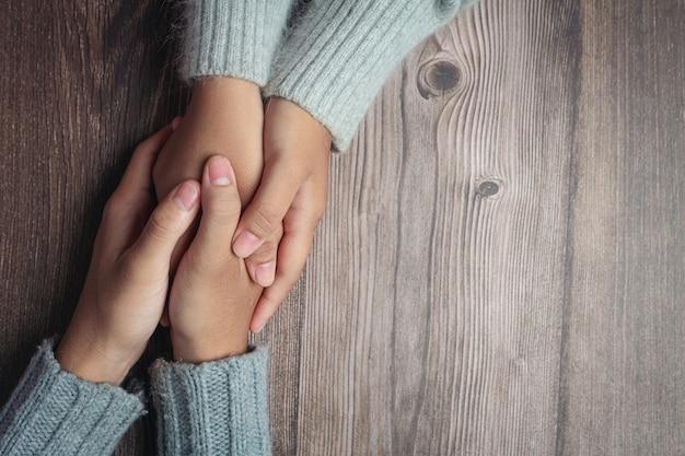 Zwei leute, die hände zusammen mit liebe und wärme auf holztisch halten