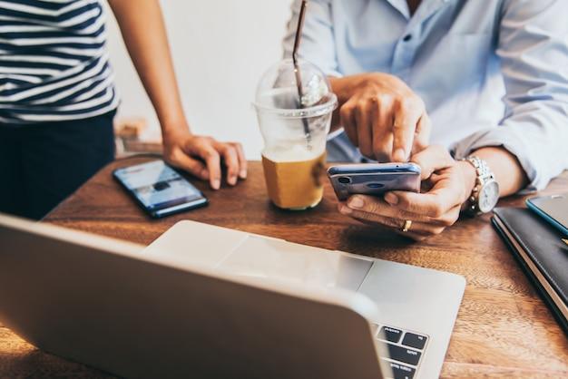 Zwei leute, die mobile beim treffen in der kaffeestube für kmu-inhaberjob verwenden