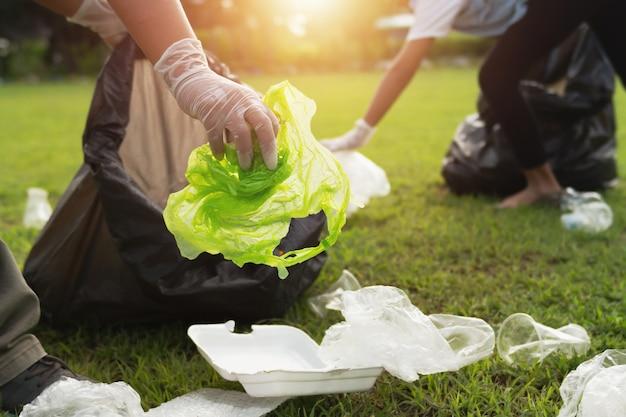 Zwei leute, die plastikflasche des abfalls in schwarze tasche am park im morgenlicht halten