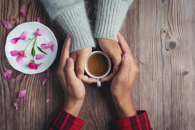 Zwei leute, die tasse kaffee in den händen mit liebe und wärme auf holztisch halten