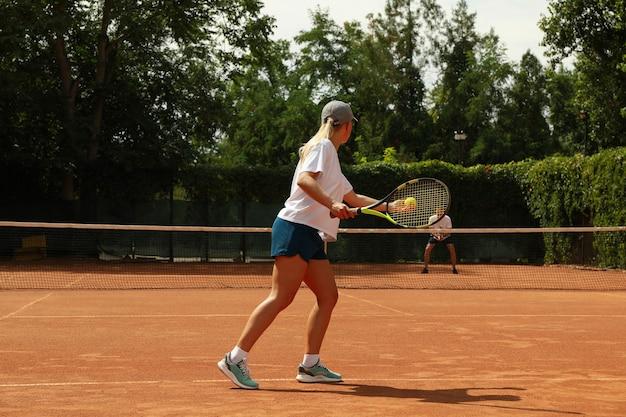 Zwei leute, die tennis auf sandplatz spielen