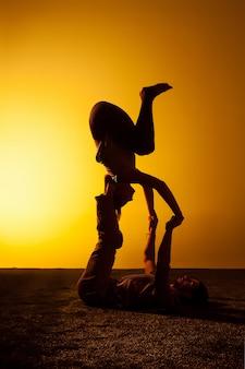 Zwei leute, die yoga im sonnenuntergangslicht praktizieren