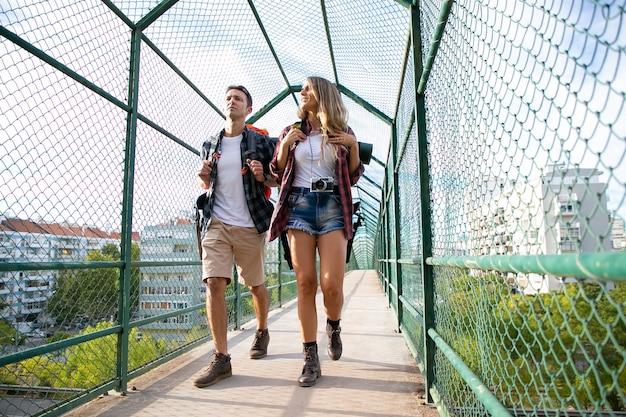 Zwei leute gehen auf brücke, umgeben von grünem gitter. kaukasischer mann und frau, die rucksäcke tragen und durch weg gehen. backpacking tourismus, abenteuer und sommerurlaub konzept