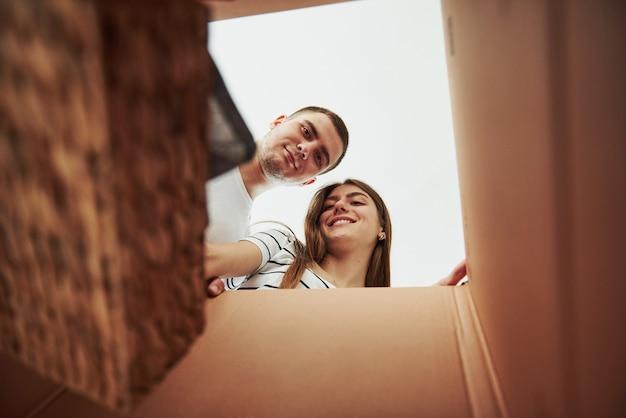 Zwei leute schauen in die kiste hinunter. konzeption des umzugs.