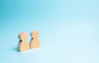 Zwei Leute stehen zusammen und reden miteinander. Zwei Holzfiguren von Menschen führen ein Gespräch