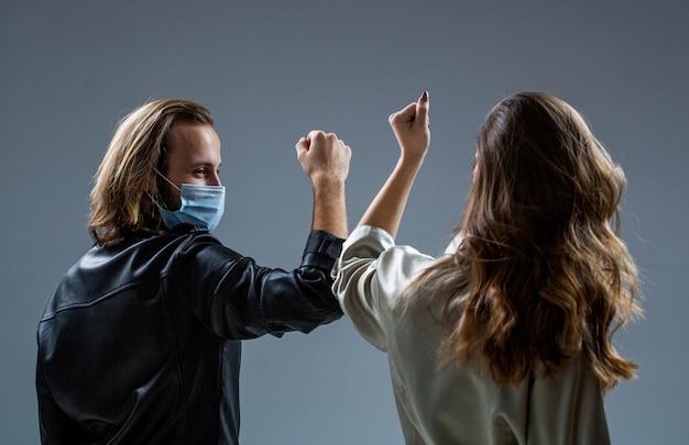 Zwei leute stoßen an die ellbogen. coronavirus epidemie. freunde in sicherheitsmaske. junges paar trägt gesichtsmasken. mädchen und kerl grüßen mit ellbogen. neues reales leben. coronavirus quarantäne. ellbogen stoßen.