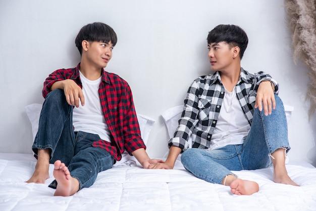 Zwei liebe junge männer saßen auf dem bett, hielten sich an den händen und sahen sich an.