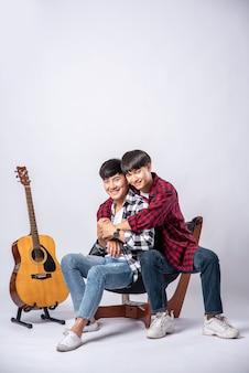 Zwei liebe junge männer saßen, kuschelten sich auf einen stuhl und hatten eine gitarre daneben.