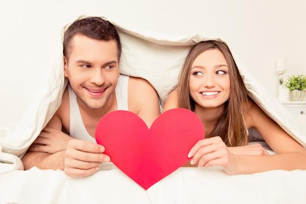 Zwei liebende, die unter decke liegen und rotes papierherz halten