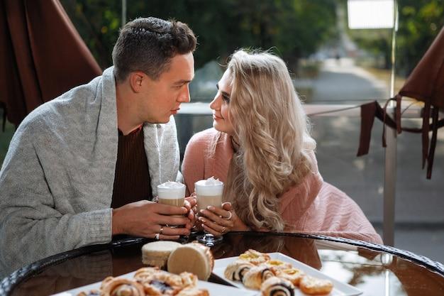 Zwei liebende, ein mann und eine frau an einem tisch in einem café. umarmen, streicheln, latte trinken. glückliches traditionelles paar, familienglück.