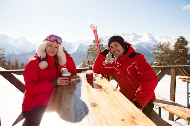 Zwei liebhaber und freunde genießen einen drink in der bar im skigebiet.