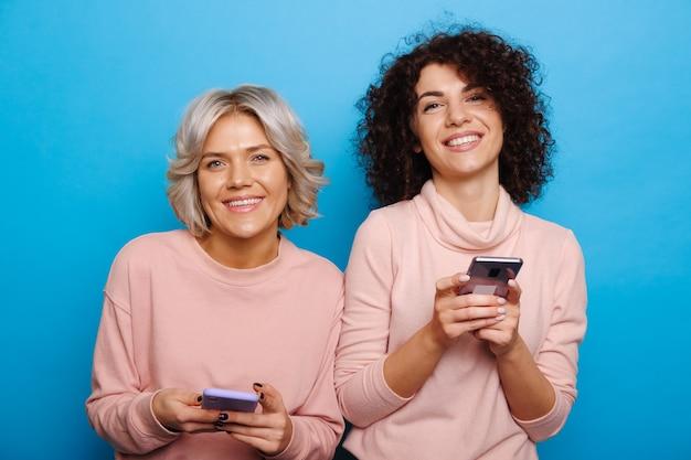 Zwei lockige kaukasische frauen plaudern und lächeln in die kamera an einer blauen wand