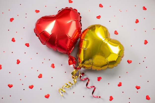 Zwei luftballons aus herzförmiger folie. liebeskonzept. valentinstag