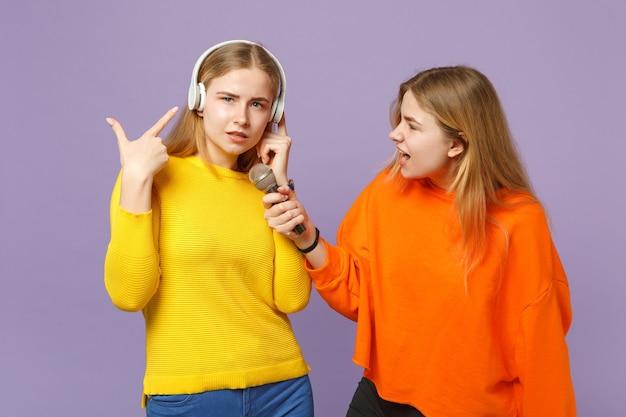 Zwei lustige blonde zwillingsschwestern mädchen in bunten kleidern hören musik mit kopfhörern, singen lied im mikrofon einzeln auf violettblauer wand. menschen-familien-lifestyle-konzept.