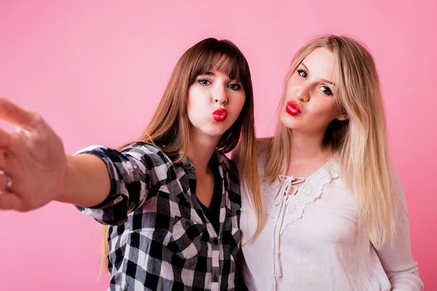 Zwei lustige frauen, die selbstporträt machen und küsse senden