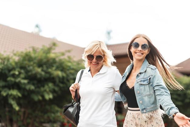 Zwei lustige frauen mit einem lächeln in sonnenbrille in einem weißen poloshirt und einer jeansjacke gehen im freien spazieren. glückliche mutter mit lächelnder tochter reisen zusammen auf dem lande