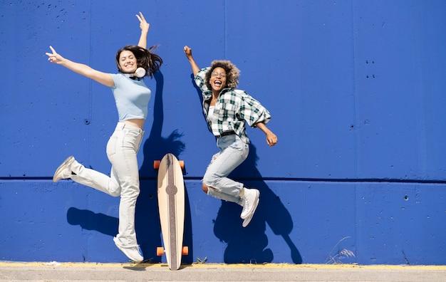 Zwei lustige frauen springen zusammen auf eine blaue wand, hören musik-kopfhörer, skateboard