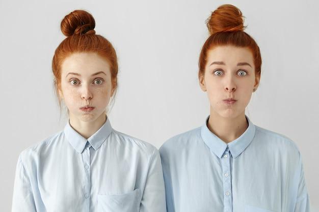 Zwei lustige junge europäische frauen mit käferaugen und gleichen frisuren, gekleidet in identische hemden