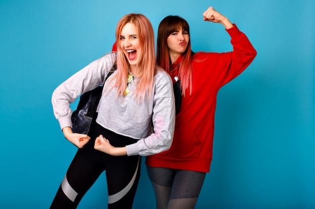 Zwei lustige junge hipsterfrau, die bizeps, blaue wand, sportliche fitnesskleidung, aufgeregte emotionen zeigt, paar, das zusammen verrückt wird.